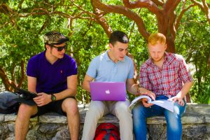 Three male students with devices and book sitting outside studying